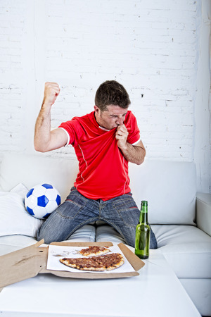 young man watching football game on television kissing team jersey shield celebrating goal crazy happy jumping on sofa couch at home with ball and beer bottle with pizza excited