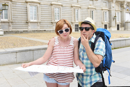 loosing: young tourist couple reading city map looking lost and confused loosing orientation with girl carrying travel backpack and man in frustrated face expression while visiting Madrid in Spain