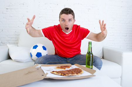 disbelief: young man alone gesturing in stress wearing team jersey watching football game on television at home living room sofa couch with pizza and beer excited  in disbelief face expression