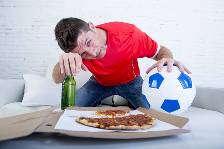 young drunk soccer supporter man holding ball and beer bottle watching football game on television sitting at home couch looking dejected , sad and disappointed for failure or defeat