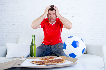 dejected: young soccer supporter man with beer bottle and ball watching football game on television at home couch dejected sad and disappointed for failure or defeat hands on his head