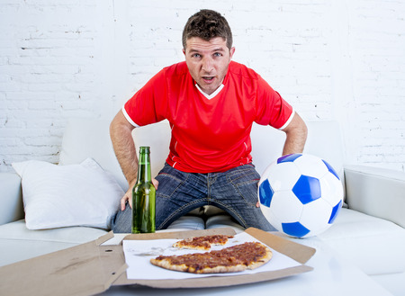 disbelief: young man alone stressed and anxious wearing team jersey watching football game on television at home living room sofa couch with pizza and beer excited  in disbelief face expression