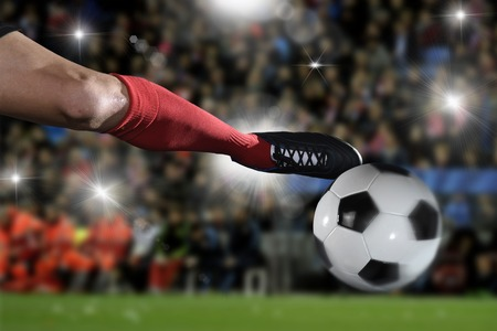 flare up: close up leg and soccer shoe of football player in action kicking ball wearing red jersey and sock playing on stadium with audience flashes  and lens flare on the background