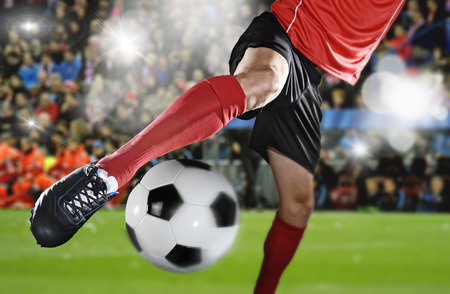 flare up: close up legs and soccer shoe of football player in action kicking ball wearing red jersey and sock playing on stadium with audience flashes  and lens flare on the background