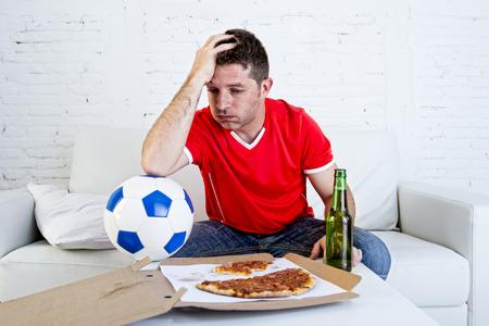 junge Fußball-Fan Mann mit Ball und Bierflasche gerade Fußballspiel im Fernsehen zu Hause Couch suchen bedrückt traurig und enttäuscht, für das Scheitern oder Niederlage tragen Trikot sitzen