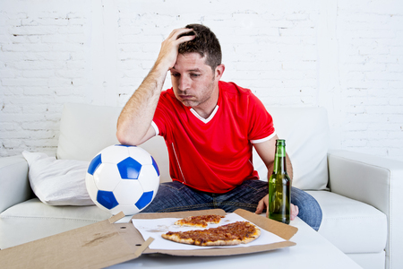 dejected: young soccer supporter man with ball and beer bottle watching football game on television sitting at home couch looking dejected sad and disappointed for failure or defeat wearing team jersey