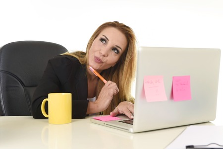 visualizing: attractive 40s blond businesswoman working at office laptop computer sitting on the desk absent minded and thoughtful smiling happy as if thinking of vacation isolated on white background