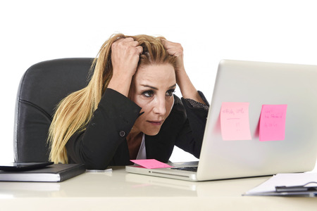 worried executive: worried attractive businesswoman in stress working with laptop computer at office desk overwhelmed and overworked suffering collapse in frustrated face expression pulling her blond hair Stock Photo