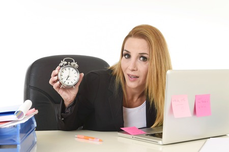 long hours: worried attractive blond businesswoman holding alarm clock sitting at office desk working with computer laptop in long hours of work and business stress concept isolated on white background Stock Photo