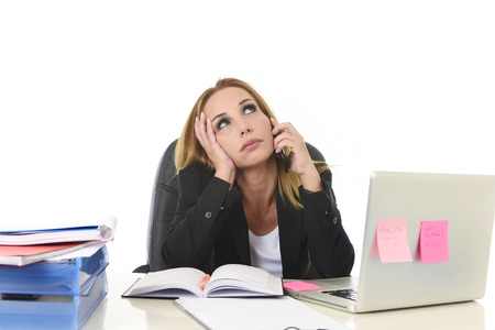 worried executive: worried attractive businesswoman in stress working with laptop computer talking on mobile phone at office desk overwhelmed and overworked suffering collapse in frustrated face expression Stock Photo