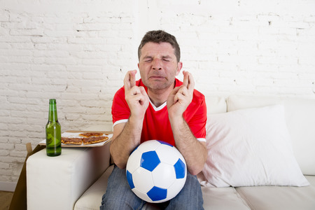 crossing fingers: young man watching football game on television nervous and excited suffering stress crossing fingers for goal on sofa couch at home with ball  beer bottle and  pizza looking crazy anxious