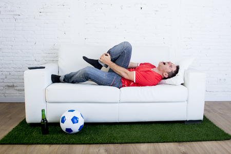 carpet grass: fanatic football fan lying on couch sofa with ball on green grass carpet emulating soccer stadium pitch mocking player in pain hurt on ankle in crazy supporter parody concept Stock Photo