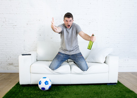 fanatic: angry football fanatic fan watching game on television holding beer gesturing upset and crazy angry complaining and screaming  at home couch on grass carpet with ball emulating stadium pitch Stock Photo