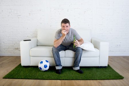 carpet grass: crazy football fan cheering watching television soccer match suffering stress nervous and excited biting his fingernails sitting on sofa couch with grass carpet and ball emulating stadium pitch Stock Photo