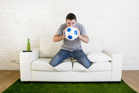 carpet grass: crazy football fan cheering watching television soccer match suffering stress nervous and excited kissing the ball hoping luck on sofa couch with grass carpet emulating stadium pitch