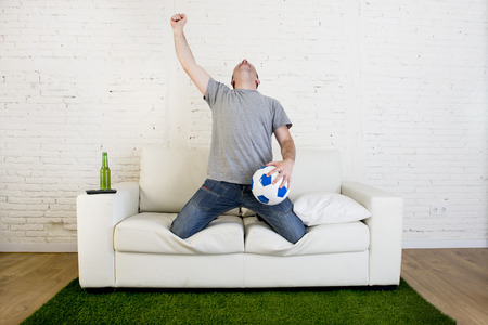 winning pitch: crazy football fan cheering happy watching television soccer match celebrating scoring goal excited and euphoric holding ball on sofa couch  on grass carpet emulating stadium pitch Stock Photo