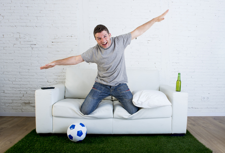 carpet grass: crazy football fan cheering happy watching television soccer match celebrating scoring goal excited and euphoric in sofa couch with ball and  grass carpet emulating stadium pitch