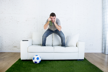 carpet grass: crazy football fan cheering watching television soccer match suffering stress nervous and excited jumping on sofa couch with ball and grass carpet emulating stadium pitch Stock Photo