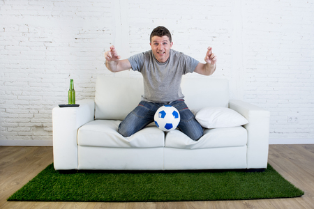 crossing fingers: football fan watching television soccer match suffering stress nervous and excited crossing fingers on home sofa couch holding ball in grass carpet emulating stadium pitch looking anxious Stock Photo