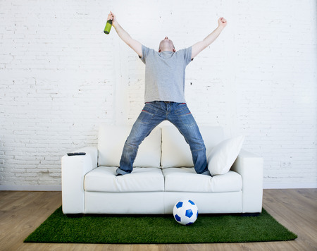 winning pitch: crazy football fan watching television soccer match celebrating scoring goal excited and euphoric holding beer jumping on sofa couch  with ball and grass carpet emulating stadium pitch