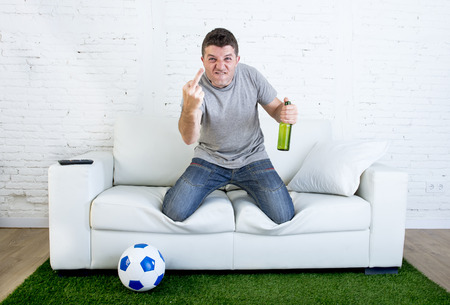 fanatic: angry football fanatic fan watching game on television at home couch holding beer gesturing upset and crazy angry giving the finger to opponent team  in grass carpet emulating stadium pitch Stock Photo