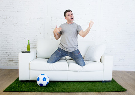 carpet grass: football fan cheering happy watching television soccer match celebrating scoring goal gesturing excited and crazy euphoric on sofa couch with ball on grass carpet emulating stadium pitch