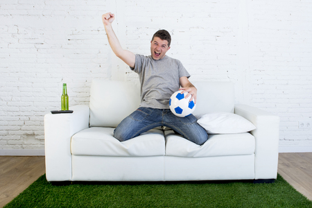 carpet grass: crazy football fan cheering happy watching television soccer match celebrating scoring goal excited and euphoric holding ball on sofa couch  on grass carpet emulating stadium pitch Stock Photo
