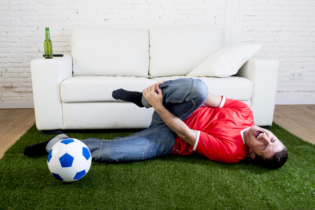 parody: fanatic football fan lying on green grass carpet emulating soccer stadium pitch mocking player in pain hurt on ankle while watching game on television in crazy supporter parody concept