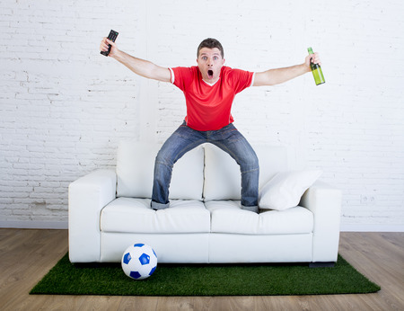 winning pitch: crazy football fan in red team jersey cheering happy watching television soccer match celebrating scoring goal excited and euphoric in sofa couch with ball on grass carpet emulating stadium pitch