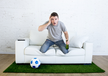 disbelief: stressed football fanatic fan watching game on tv nervous in disbelief face as if disaster comes holding beer at home couch in grass carpet and ball emulating stadium pitch