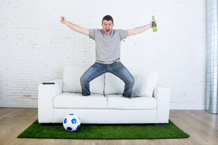 carpet grass: crazy football fan watching television soccer match celebrating scoring goal excited and euphoric holding beer jumping on sofa couch  with ball and grass carpet emulating stadium pitch