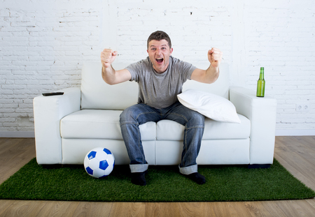 carpet grass: crazy football fan cheering happy watching television soccer match celebrating scoring goal excited and euphoric sitting on sofa couch with ball and grass carpet emulating stadium pitch