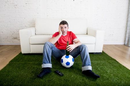carpet grass: football fan cheering watching focused television soccer match suffering stress nervous wearing red team jersey sitting off couch on grass carpet with ball emulating stadium pitch