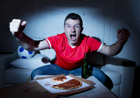 fanatic: ecstatic and fanatic football fan man watching soccer game on television in red team jersey celebrating goal crazy happy on  couch at home with ball and  beer bottle eating pizza dark light set Stock Photo
