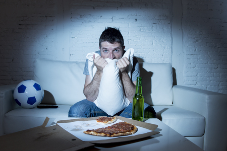 young fanatic man watching football game on television nervous and anxious covering face with pillow suffering stress on sofa couch at home with soccer ball beer bottle and pizza looking crazy