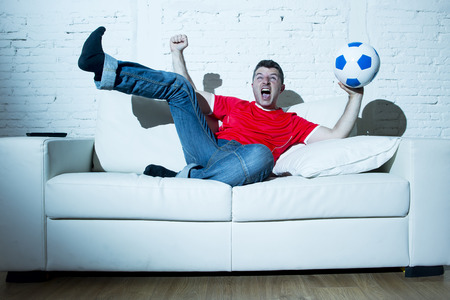 fanatic: crazy fanatic  man as football fan watching game on television wearing red team jersey celebrating goal happy and ecstatic jumping excited on sofa couch at home with ball