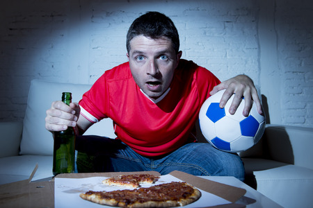 fanatic: crazy fanatic man football fan watching football game on television wearing red team jersey suffering nervous and stress on sofa couch at home holding  soccer ball drinking beer eating pizza