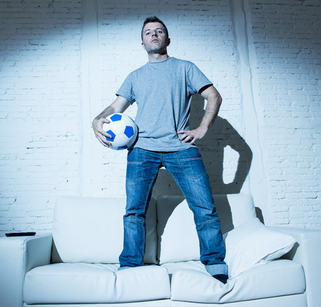 fanatic: young attractive man standing on top of home sofa couch holding ball looking cool and defiant in bad boy attitude style posing alone Stock Photo