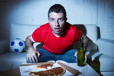 fanatic: crazy fanatic man football fan watching football game on television wearing red team jersey suffering nervous and stress on sofa couch at home with soccer ball beer bottle and pizza Stock Photo