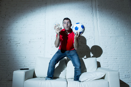 fanatic man jumping happy on sofa couch holding money and ball in his hands watching soccer game on television ecstatic and excited winning on line bet in internet gambling concept Stockfoto