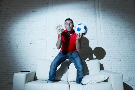 L'homme fanatique sautant heureux sur le canapé canapé tenant de l'argent et la balle dans ses mains à regarder match de football à la télévision extatique et excité gagnant sur pari en ligne sur Internet concept de jeu Banque d'images - 58105952