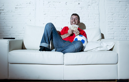 fanatic: fanatic man lying happy on sofa couch holding money and ball in his hands watching soccer game on television ecstatic and excited winning on line bet in internet gambling concept