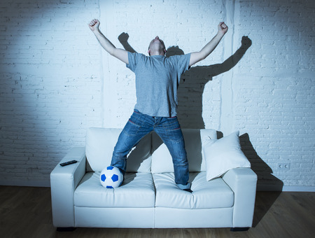 ecstasy: young man fanatic and crazy football fan watching television soccer match with ball jumping on sofa couch screaming happy celebrating goal in ecstasy Stock Photo