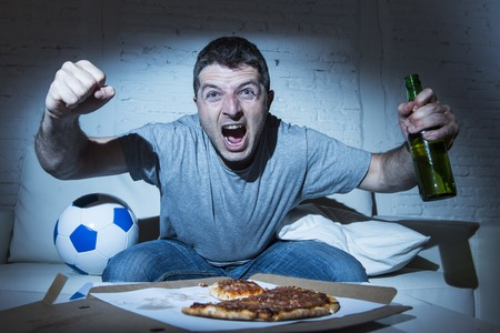 fanatic: young man fanatic and crazy football fan watching television soccer match alone screaming happy celebrating scoring goal in glad and ecstatic face expression with beer bottle and pizza
