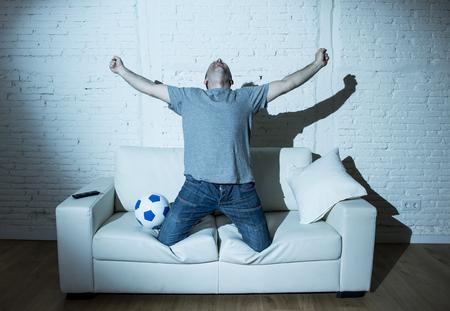 éxtasis: fanático del hombre joven y aficionado al fútbol loco viendo el partido de fútbol la televisión solos gritando feliz celebración de gol en contenta en éxtasis con la bola en el sofá en casa