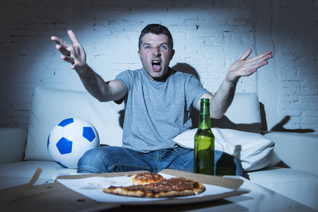 dejected: young supporter man watching football game on television sitting at home couch with ball beer and pizza in stress dejected and disappointed for failure shouting and complaining Stock Photo