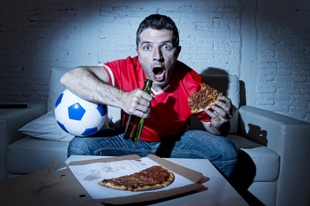 fanatic: crazy fanatic man football fan watching football game on television wearing red team jersey nervous and surprised on sofa couch at home holding  soccer ball drinking beer eating pizza