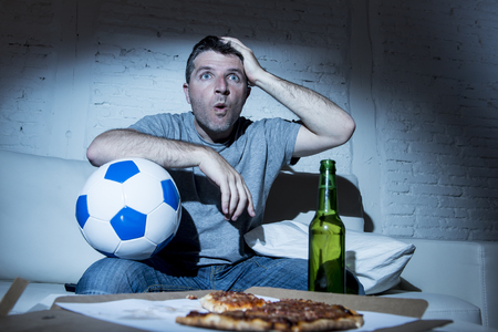 fanatic: young fanatic man watching football game on television nervous and excited suffering stress on sofa couch at home with ball beer bottle and pizza looking anxious and crazy