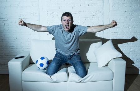 screaming: young man fanatic and crazy football fan watching television soccer match alone screaming happy celebrating scoring goal in glad and ecstatic face expression with ball on home couch