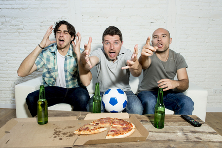 complaining: group of friends fanatic football fans watching soccer game on television with beer bottles and pizza suffering stress and crazy nervous on couch screaming and complaining